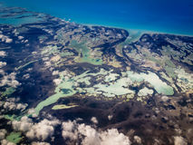 Den flyg- sikten av karibiska olika toner av gräsplaner och deppigheter marbleized vid landkonturer Royaltyfri Fotografi