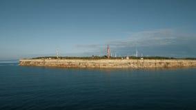 Den flyg- sikten av kustlinjen med vaggar från havet och på för fyr- och vindturbinen för land de gamla generatorerna för makt lager videofilmer