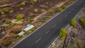 Den flyg- sikten av kvinnan kör längs den öde asfaltvägen på solnedgången Berg på bakgrunden stock video