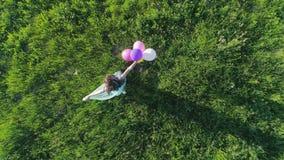 Den flyg- sikten av den lyckliga flickan ser kameran och snurr med kulöra ballonger i händer på bakgrund av gräs lager videofilmer
