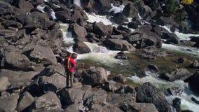 Den flyg- sikten av mannen som står av en vattenfallflod med, vaggar framme, floden arkivfilmer