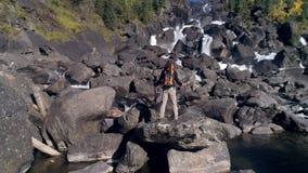 Den flyg- sikten av mannen som står av en vattenfallflod med, vaggar framme, träd stock video