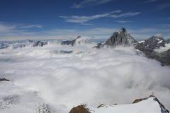 Den flyg- sikten av molnet täckte bergskedjor i Zermatt Arkivfoto