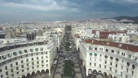 Den flyg- sikten av plazaen med folk under en molnig himmel, Thessaloniki Grekland, flyttar sig framåtriktat med surret