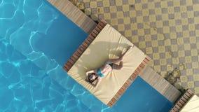Den flyg- sikten av den sexiga flickan i glasögon och swimwear tycker om sommarlögnerna nära simbassäng med blått vatten stock video
