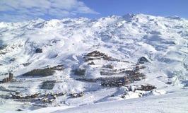 Den flyg- sikten av skidar bysemesterorten i höga snöig franska fjällängar Arkivfoto
