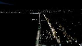 Den flyg- sikten av staden på natten, Thessaloniki Grekland, flyttar sig framåtriktat med surret
