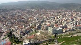 Den flyg- sikten av den stads- miljön med fyrkanten och parkerar, staden av Veria Grekland, flyttning tillbaka och upp med surret