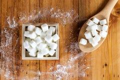 Den flyg- sikten av Sugar Cubes i fyrkanten formad bunke och skeden med rått socker spiller över i träbakgrund Arkivfoton