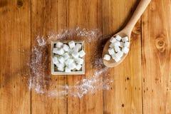 Den flyg- sikten av Sugar Cubes i fyrkanten formad bunke och skeden med rått socker spiller över i träbakgrund Arkivfoto