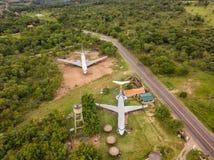 Den flyg- sikten av två kasserade flygplan på en privat lott Täpporna runt om flygplanet är till salu Royaltyfri Bild