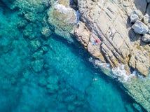 Den flyg- sikten av vaggar på havet Simmare badare som svävar på vattnet eople som solbadar på handduken Arkivfoto