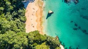 Den flyg- sikten på en liten strand som förbi omges, vaggar och skogen Coromandel, Nya Zeeland Arkivfoton
