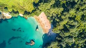 Den flyg- sikten på en liten strand som förbi omges, vaggar och skogen Coromandel, Nya Zeeland Arkivfoto