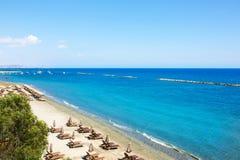 Den flyg- sikten på stolar för en strand och paraplyer på sand sätter på land Royaltyfria Bilder