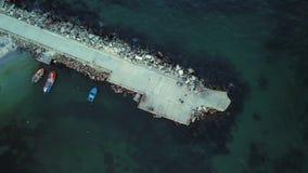 Den flyg- sikten zoomar in av en liten pir i ett hav, lilla det förtöjde fiskarefartyget lager videofilmer
