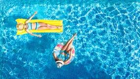 Den flyg- surrsikten av barn i simbassäng från över, lyckliga ungar simmar på uppblåsbara cirkeldonuts, flickor har gyckel i vatt royaltyfri bild