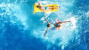 Den flyg- surrsikten av barn i simbassäng från över, lyckliga ungar simmar på uppblåsbara cirkeldonuts, flickor har gyckel i vatt arkivfoton