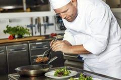 Den fokuserade kocken förbereder biffmaträtten på den gourmet- restaurangen royaltyfri bild