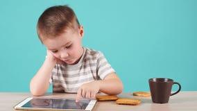 Den fokuserade unga pojken använder minnestavlan för att lära nya program stock video