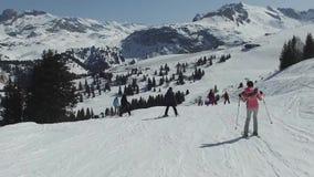 Den folkatt skida och snowboardingen på en lutning på skidar semesterorten stock video