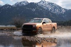 Den Ford Ranger varubilen är av att roading i gyttjan arkivbilder