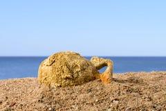 Den forntida amfora som ligger på sanden mot den blåa himlen, grundar i Grekland arkivfoto