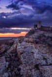 Den forntida citadellen av en stenig kulle på solnedgången mot dramatiska moln med rikt vaggar överst bildande i förgrunden royaltyfri foto