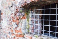 Den forntida det tegelstenväggen och fönstret låste med metallstänger Arkivbilder