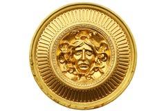 Den forntida guld- krigareskölden som isoleras på vit bakgrund, cirklar den glansiga stålskölden med framsidan av mänsklig solide Royaltyfri Fotografi