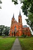 Den forntida kyrkan som göras från röda briks, och den fridsamma kyrkan parkerar i den lilla Polen staden Rajgrod, Polen Royaltyfri Bild