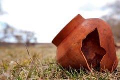 Den forntida lerakrukan delas i fältet Övergett urgammalt för tegelplatta Lerakrukan är bruten Arkivbilder