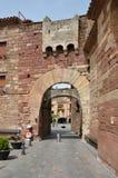 Den forntida porten i den spanska röda staden Prades Royaltyfri Bild