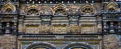 Den forntida tegelstenväggen, den utsmyckade stenhuggeriarbetet, rich färgar Arkivbilder