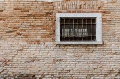 Den forntida tegelstenväggen texturerar Fönster med gallret och räcke Arkivfoton
