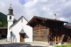 Den forntida traditionella chalet och kyrkan längs Furkastrassen munster Arkivfoto