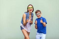 Den fräkniga syskongruppen i tillfälliga t-skjortor som bär moderiktiga exponeringsglas och tillsammans poserar över ljus - grön  Arkivfoton