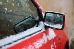 Den främre delen av den röda bilen med sideviewspegeln Arkivbilder