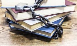 Den främre sikten av böcker låste med hänglåset och kedjor royaltyfri foto
