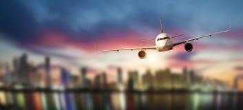 Den främre sikten av det kommersiella flygplanet, gör suddig den moderna staden på bakgrund royaltyfri foto