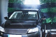 Den främre sikten av en carwash som gör ren en bil med att rotera, borstar royaltyfria foton