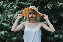 Den främre sikten av flickan i en vit skjorta i bakgrunden är en vägg av häckar Royaltyfri Foto