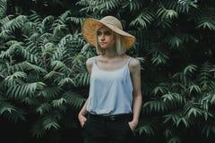 Den främre sikten av flickan i en vit skjorta i bakgrunden är en vägg av häckar Arkivfoto