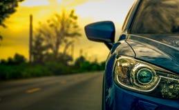 Den främre sikten av lyxblått pressar samman SUV bilen med sporten och den moderna designen som parkeras på asfaltvägen på solned royaltyfri fotografi