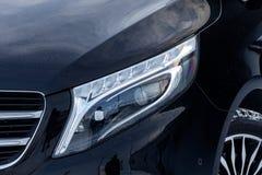 Den främre sikten av nytt en dyr Mercedes Benz V-grupp minivan ledde pannlampan, en lång svart limousinemodell royaltyfri fotografi