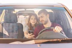Den främre sikten av den orakade manliga chauffören sitter på hjulet och kör hans bil, medan hans fru sitter på baksätet, rymmer  royaltyfri bild