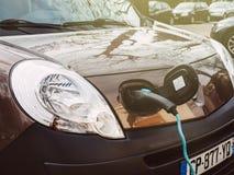 Den främre sikten pluggade in den Renault kortkort-skåpbilen elbilen på streen Royaltyfria Foton