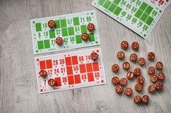 Den framkallande gamla lottot för bingotabellleken spelar med träbeståndsdelar och cards bingo på en träbakgrund Royaltyfri Fotografi
