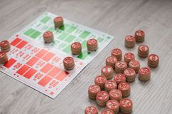 Den framkallande gamla lottot för bingotabellleken spelar med träbeståndsdelar och cards bingo på en träbakgrund Royaltyfri Foto