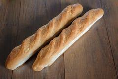Den franska bagetten bantar den hela kornbagetten på tabellen Royaltyfri Foto